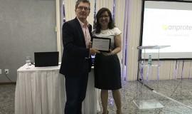 Sheila Pires, superintendente executiva da Anprotec, entrega placa de reconhecimento a Sergio Risola, Diretor de Empresas durante a gestão 2016-17.